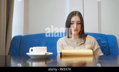 Young woman in cafe chooses lunch flipping through the menu - Stock Photo