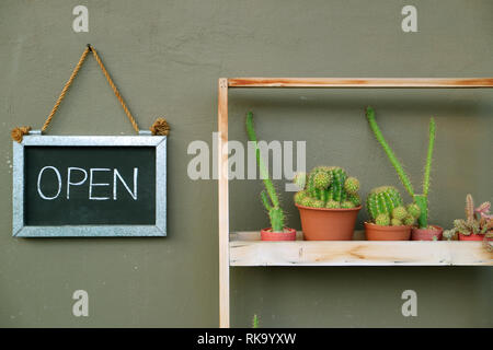 OPEN sign board hanging on the cafe outer wall beside the succulent plants shelf - Stock Photo