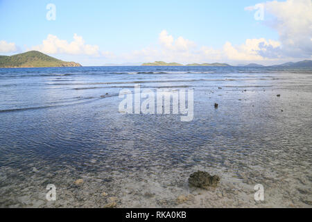 Low tide at sunset on a beach of St Thomas Island, US VI. Waves rolling in from the sea and faraway islands on the horizon. - Stock Photo
