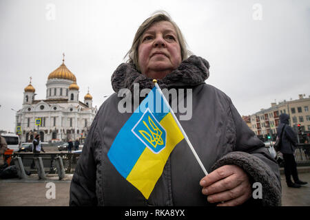 Moscow, Russia. 10 February, 2019: A woman takes part in Mothers' Anger March, an event in support of political prisoners in Moscow. A woman holds Ukrainian flag on background of the Cathedral of Christ the Saviour in central Moscow, Russia Credit: Nikolay Vinokurov/Alamy Live News - Stock Photo