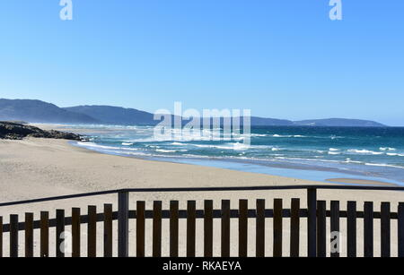 Wild beach with wooden handrail, golden sand and blue sea with waves. Sunny day, clear sky, Galicia, Coruna Province, Spain. - Stock Photo