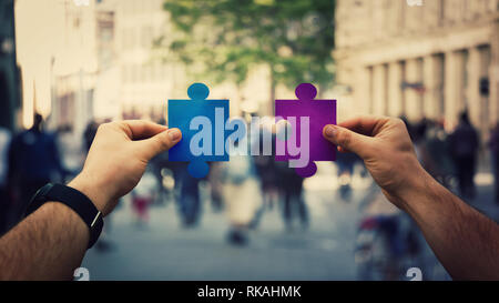 Two hands holding different colored puzzle pieces, unite jigsaw over a crowded street background. Business solutions, success and strategy diversity c - Stock Photo