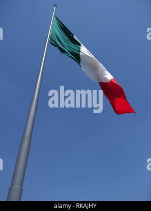 Beautiful national maxican flag on beach at bay of Pacific Ocean in Acapulco city, Mexico with clear blue sky - vertical - Stock Photo