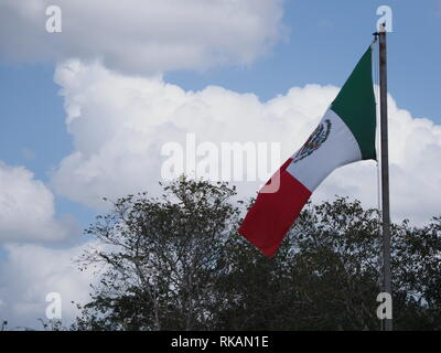 National maxican flag at Chichen Itza city near scenic archaeological site in Mexico with trees and cloudy sky - Stock Photo