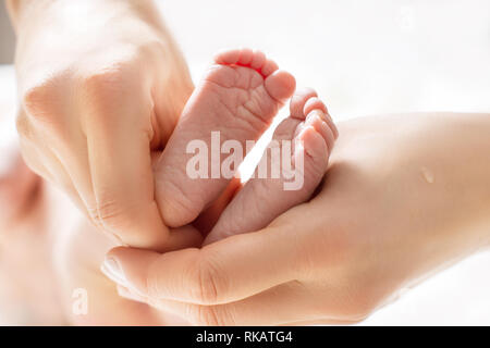 Mom massages the legs of a newborn baby.  Baby feet in mother hands. Tiny new born baby's feet on female hands closeup - Stock Photo