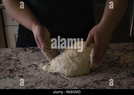 Baker kneading sourdough bread dough before allowing it to rise further. - Stock Photo