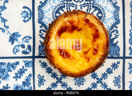 A Single Pastel de Nata On Traditional Blue And White Azulejo Tile Towel Background - Stock Photo