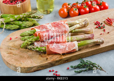 Fresh organic asparagus wrapped in Prosciutto ham on a cutting board. - Stock Photo