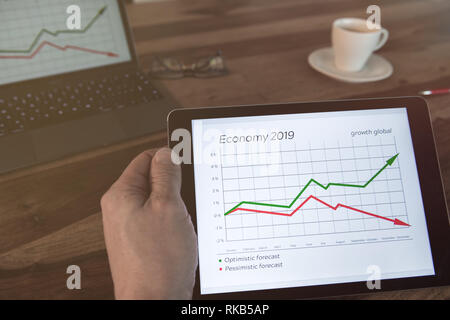 Man is sitting at the table with a tablet in his hand. Economic data is displayed. - Stock Photo