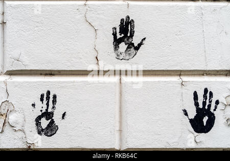 3 three black palm imprints on white large bricks with white peeling paint - high quality texture / background - Stock Photo