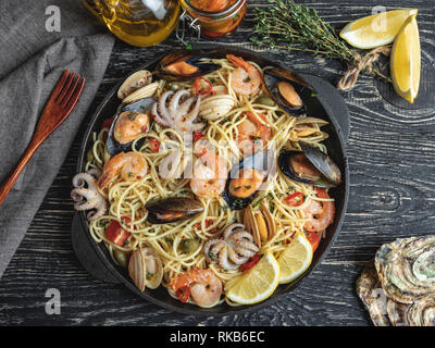Cooked pasta with clams, shrimps, baby octopus, mussels tomato on a frying pan , spaghetti. Close up - Stock Photo