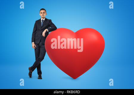 Businessman and big red heart model on blue background - Stock Photo