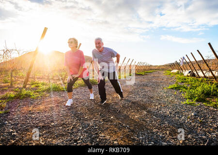 Two mature people man and woman enjoying sport fitness activity outdoor in the nature countryside at sunset doing stretching and balance exercise - we - Stock Photo