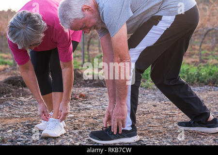 Couple of senior adult caucasian people man and woman doing fitness running exercises outdoor to stay healthy and hace care of their bodies - wellness - Stock Photo