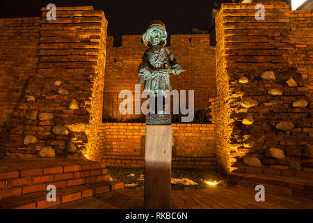 Little Insurgent statue against old city wall at night in Warsaw, Poland. Monument to the child soldiers who fought and died during the Warsaw Uprisin - Stock Photo