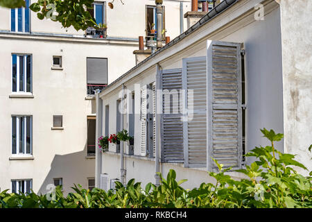 Paris apartments with white wooden shutters on the windows,seen from Promenade Plantée an elevated disused railway, Paris ,France - Stock Photo