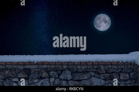 Stone wall covered by fresh snow during a winter. A starry sky with the full Moon appears in the background - Stock Photo