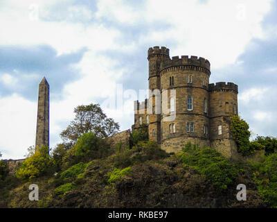 Castle in Edinburgh with obelisk on the mountainside. - Stock Photo