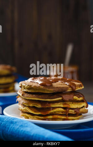 Pumpkin pancakes with caramel on wooden background - Stock Photo