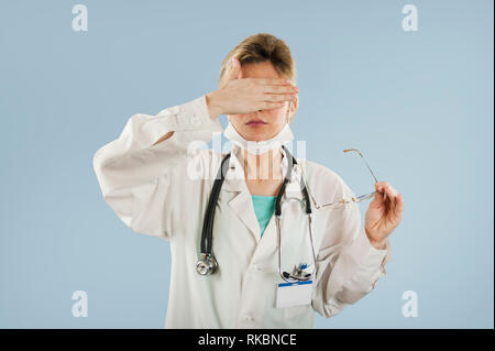 Young doctor girl closes eyes with a hand on a blue isolated
