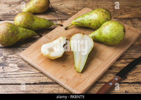 Fresh juicy Pears Conference whole and cut by slides on wooden rustic background - Stock Photo