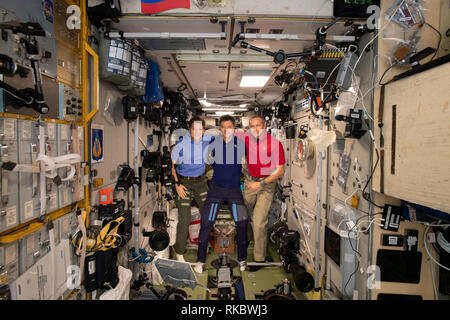 International Space Station Expedition 58 crew members gather inside the Zvezda service module for a crew portrait December 29, 2018  in Earth Orbit. From left are: NASA astronaut Anne McClain, Roscosmos cosmonaut Oleg Kononenko and Canadian Space Agency astronaut David Saint-Jacques. - Stock Photo