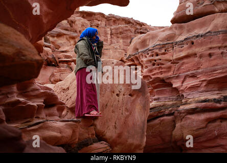 A Bedouin girl stands on rock formations in Egypt's Coloured Canyon, located near the Sinai town of Nuweiba, Egypt. (Photo/Hasan Jamali) - Stock Photo