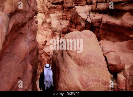 A Bedouin man walks through Egypt's Coloured Canyon near Nuweiba in the Sinai Peninsula.(Photo/Hasan Jamali) - Stock Photo