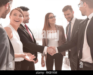 Happy businessman reaching hand out in front of his team in the office - Stock Photo