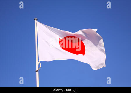 Japan flag waving on the wind with background of blue sky - Stock Photo
