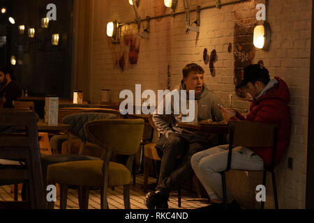 Two young men sat at a restaurant table relaxing,Leeds,West Yorkshire,UK. - Stock Photo