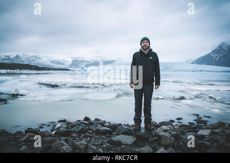 Young man standing in front of Fjallsarlon iceberg lagoon at the south end of the glacier Vatnajokull, with floating icebergs that calve from the edge - Stock Photo