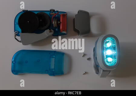 Interior of a dyno torch, dynamo wind up flashlight hand pressing crank, squeezing a handle, mechanically powered three LED flashlight - Stock Photo