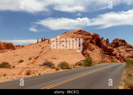 Visitors climbing a large outcrop beside Mouse's Tank Road, Valley of Fire State Park, Overton, Nevada, USA. - Stock Photo
