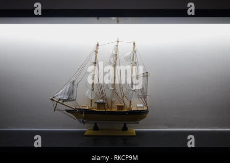 Model Sailboat Frigate Sitting on Display Shelf Lights Black White Elegant Decoration Centered - Stock Photo
