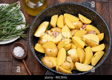 Potato wedges with sea salt, rosemary, olive oil on skillet. Old wooden background - Stock Photo