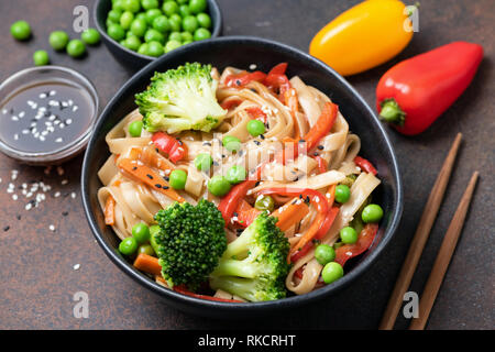 Asian noodle stir fry with vegetables in bowl. Udon noodles with broccoli, pepper, carrot and green peas - Stock Photo