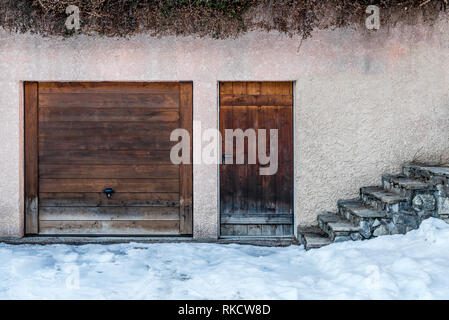 Wood garage and entry doors inset to rendered stone wall of outbuilding with stone stairs steps leading away to main building - Stock Photo