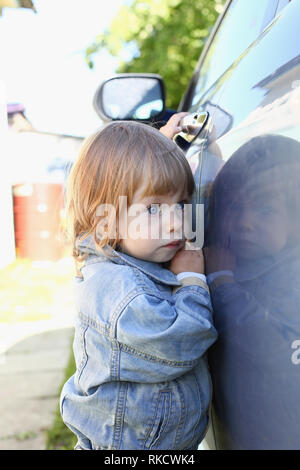 Little fashion child holds the car handle in a jeans jacket - Stock Photo