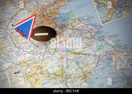Macro shot of a flag and football placed on Gillette Stadium in a map. - Stock Photo