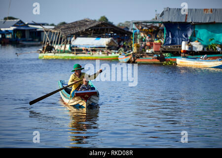 Tonlé Sap Lake,  Cambodia. 19th December, 2018. A fisherwoman and her young daughter row past floating houses in the background. Photo: Bryan Watt - Stock Photo