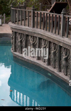 Garden lounge pool surrounded by stone sculptures and pilasters with a terrace balcony above - Stock Photo