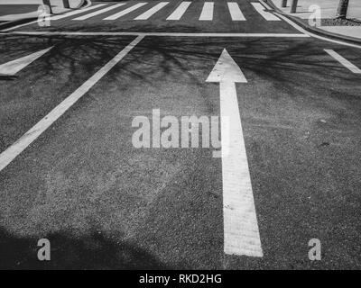 Arrows painted on the road asphalt, safety, black and white style - Stock Photo