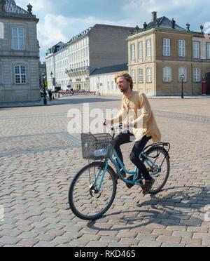 COPENHAGEN, DENMARK - JUNE 14, 2019:  Young hipster man riding city bicycle in bright sunshine at Amalienborg Palace Square, Copenhagen, Denmark, Euro