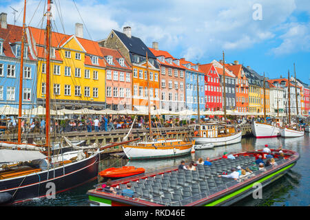 Tour boat sailing by canal with old sailboats in Nyhavn harbor, peopel walking at sunny embankment and sitting in cafes and restaurants, Copenhagen, D