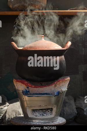 baked clay kettle with hot water on traditional stove - Stock Photo