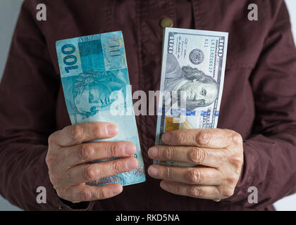 Brazilian Reais and North American currency. Dollar. Money from Brazil and United States. Old retired person paying in cash. - Stock Photo
