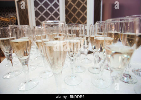 Waiter pours champagne in glasses, luxury event. - Stock Photo