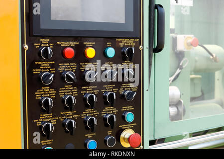 Automatic hydraulic rubber molding press machine with a control panel on the foreground. - Stock Photo