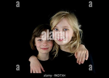 Two happy girls putting their arms around each other against a black background - Stock Photo